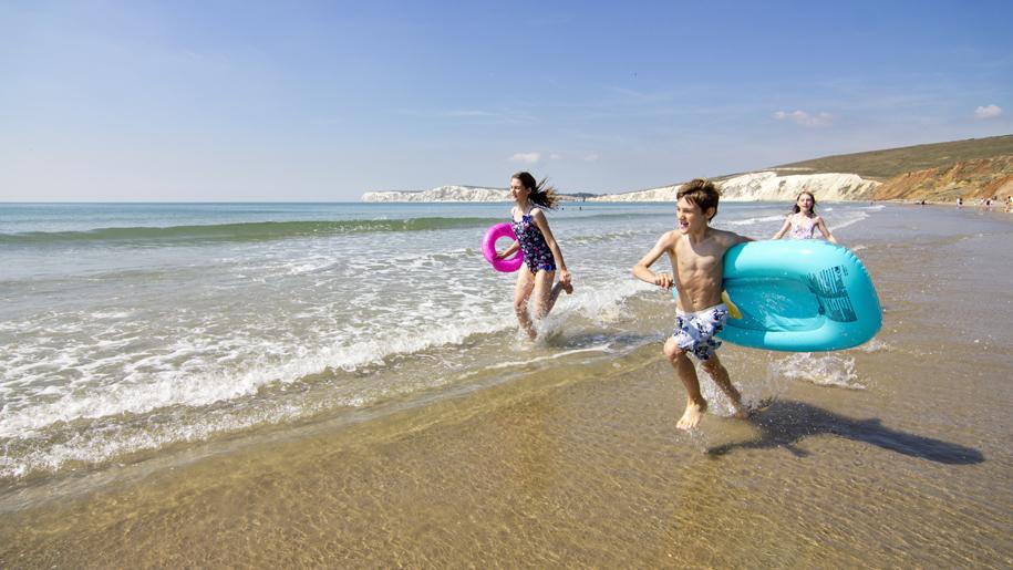 children running along the beach