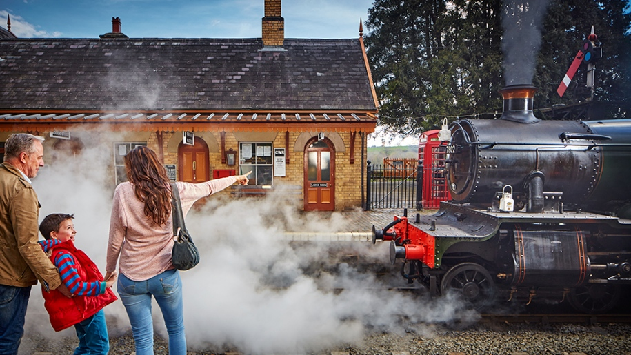 family looking at steam train