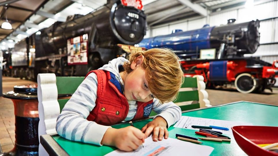 child colouring with trains in background