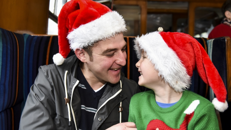father and son on train with santa hats on