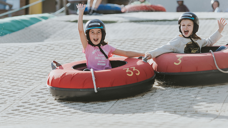 children smiling on donuts on dry slope skiing