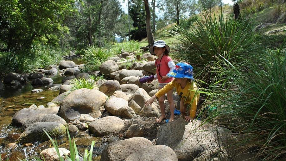 children exploring river