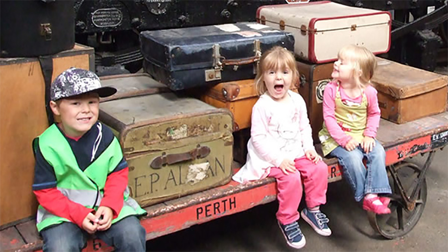 children sitting on luggage kart