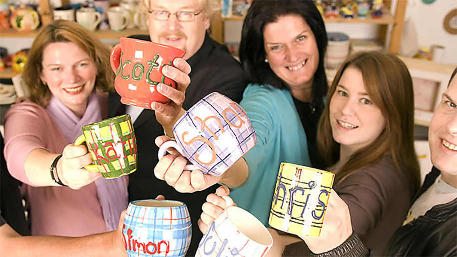 family holding mugs that they have painted