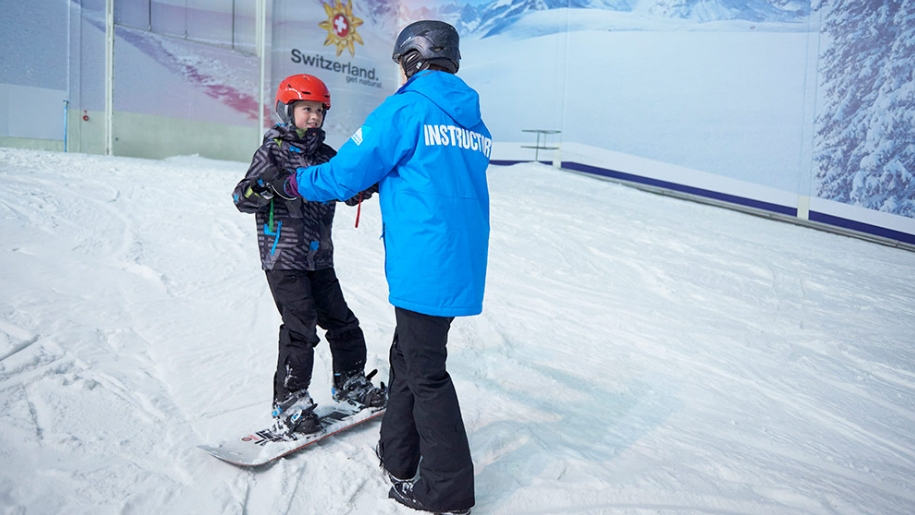 boy learning to snowboard at indoor ski slope
