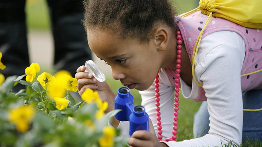 girl looking through magnifying glass at flowers
