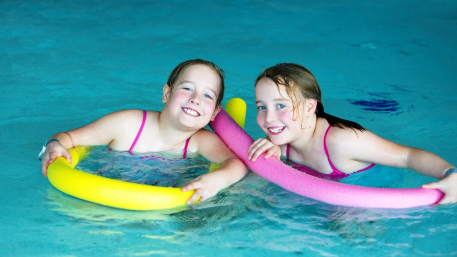 girls in swimming pool with floats