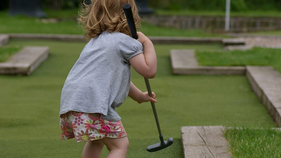 girl on miniature golf course