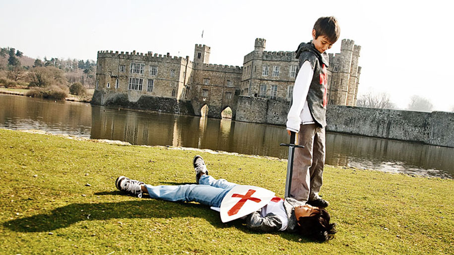 two boys dressed as knights in front of castle