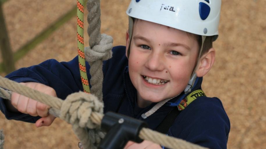 boy climbing on high ropes
