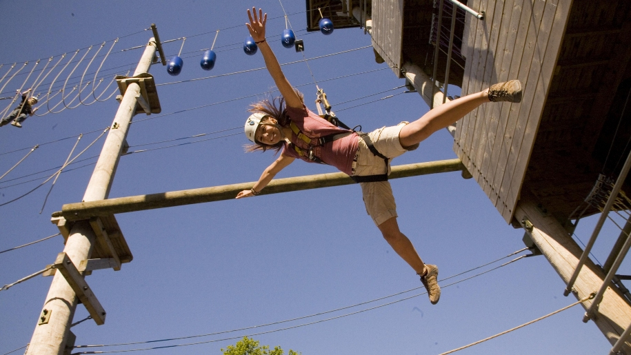 girl jumping at high ropes course