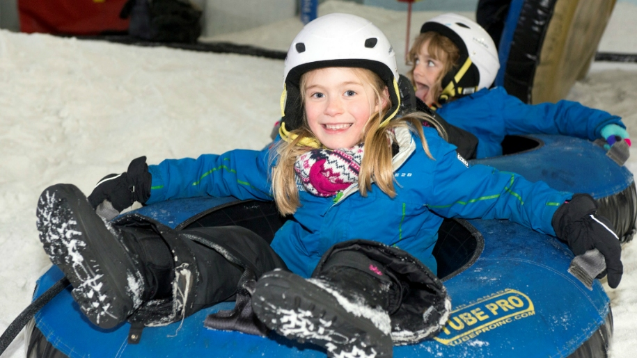 Two children in donuts on ski slope