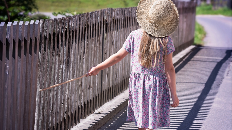 girl walking by fence