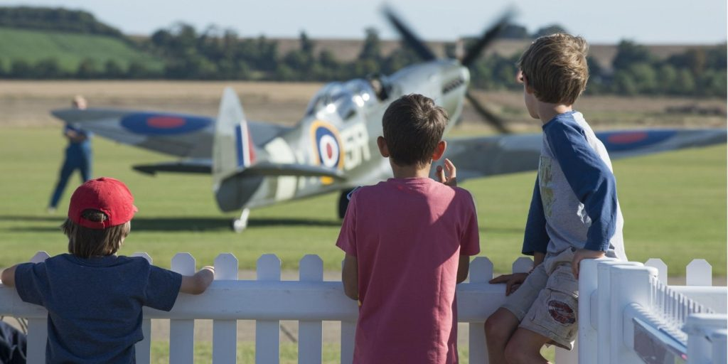 three boys looking at fighter plane