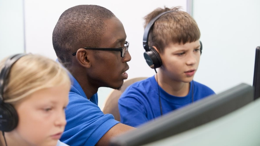 boy being taught at computer