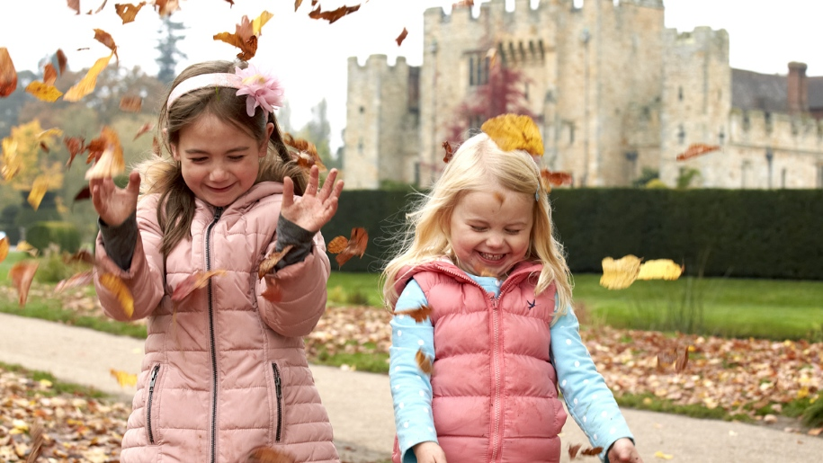 girls throwing leaves in front of castle