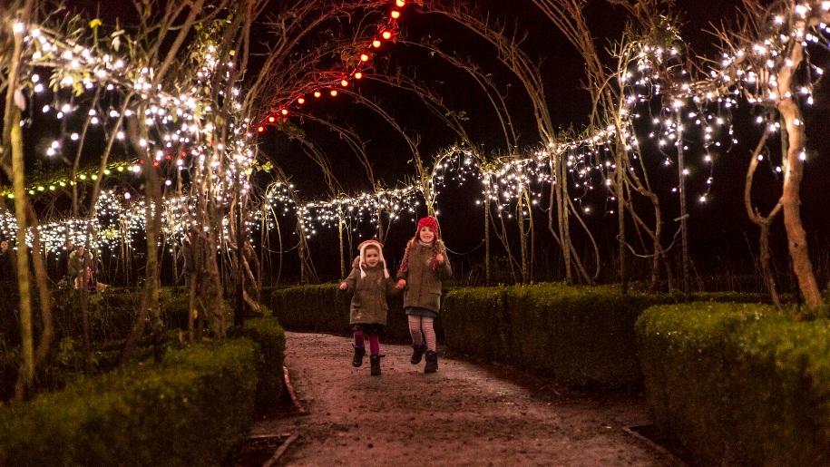 girls running under christmas lights