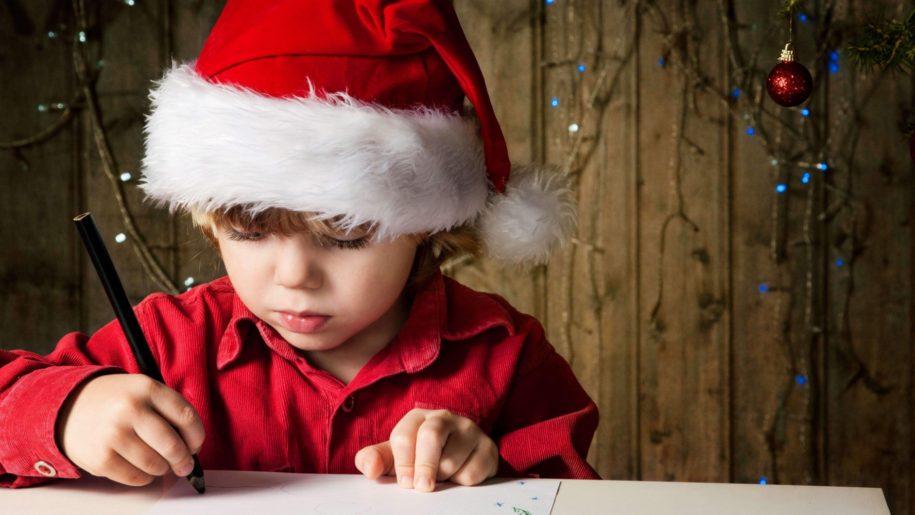 little boy in Santa hat writing Christmas letter