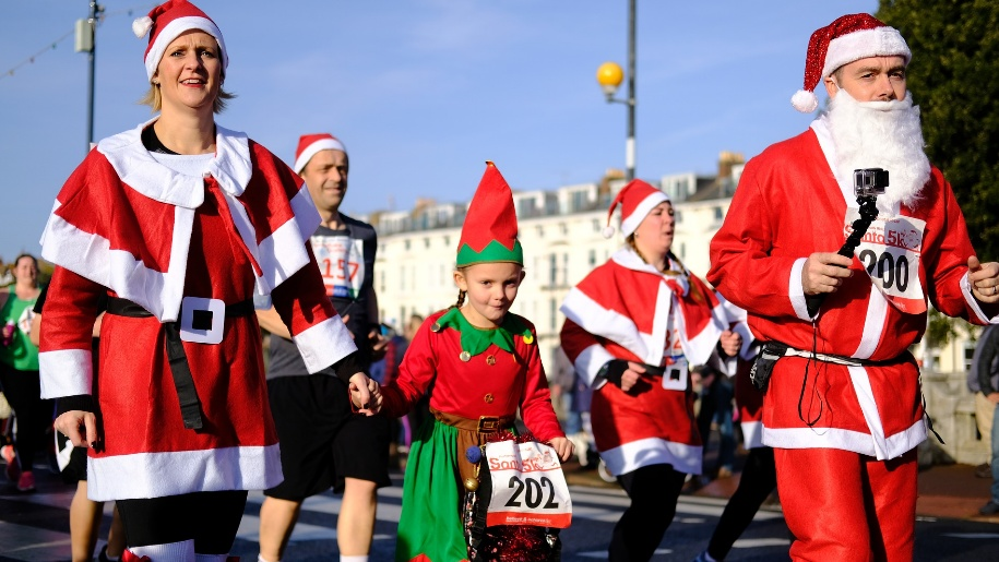 people dressed up as santa on run