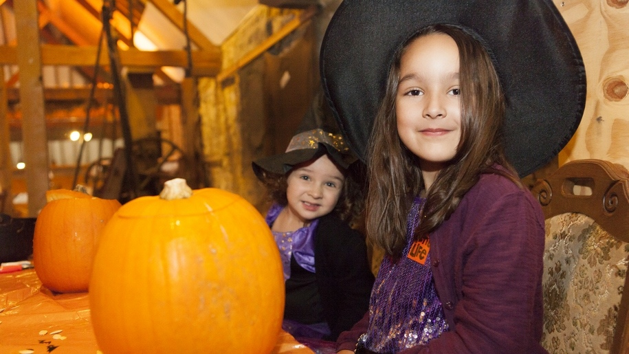 girls dressed as witches with pumpkins