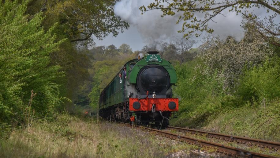 steam train going through countryside