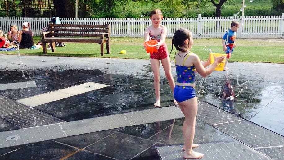 two girls playing in water fountains