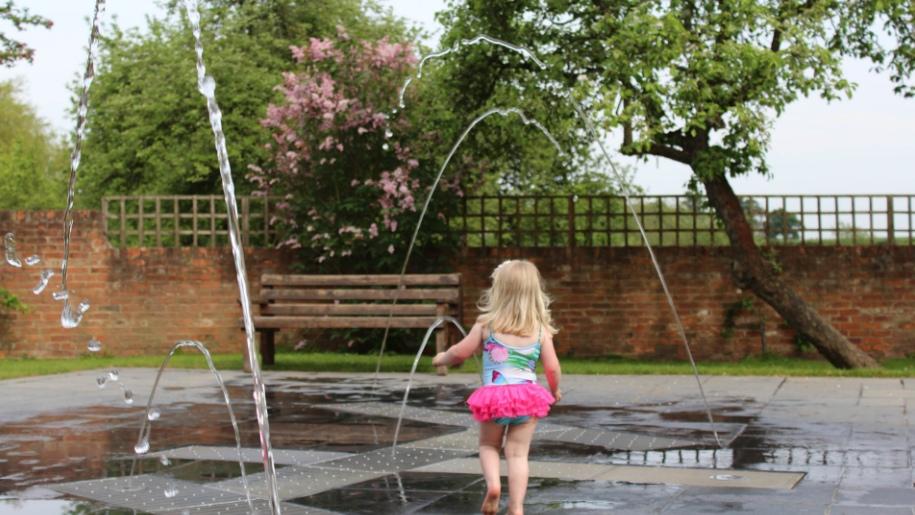 girl running through water fountains