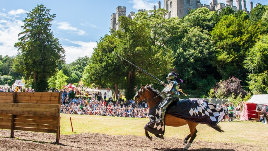Knight riding a horse in jousting contest in front of a crowd