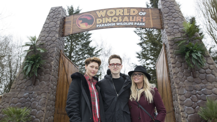 Tom Fletcher, Emma Bunton and Emma Willis in front of World of dinosaur sign
