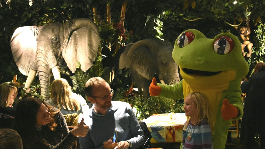 family inside the Rainforest Cafe with frog character