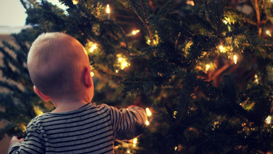toddler hanging up christmas decorations