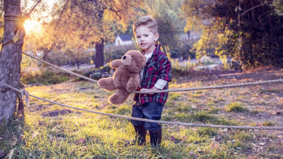 boy holding his teddy outside