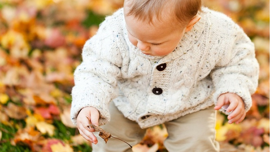 baby picking leaves off the floor