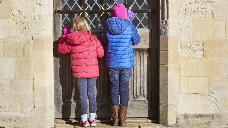 Two girls peering through a door at Anglesey Abbey