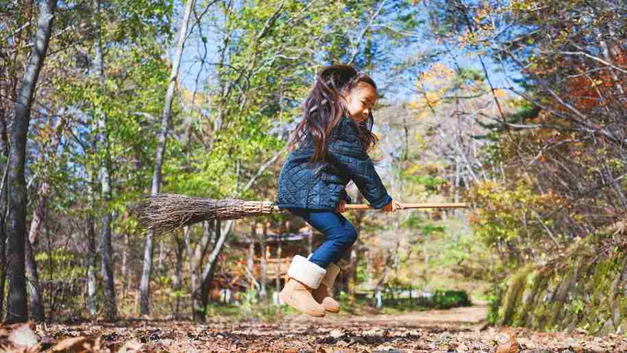 halloween girl flying on broomstick in woods