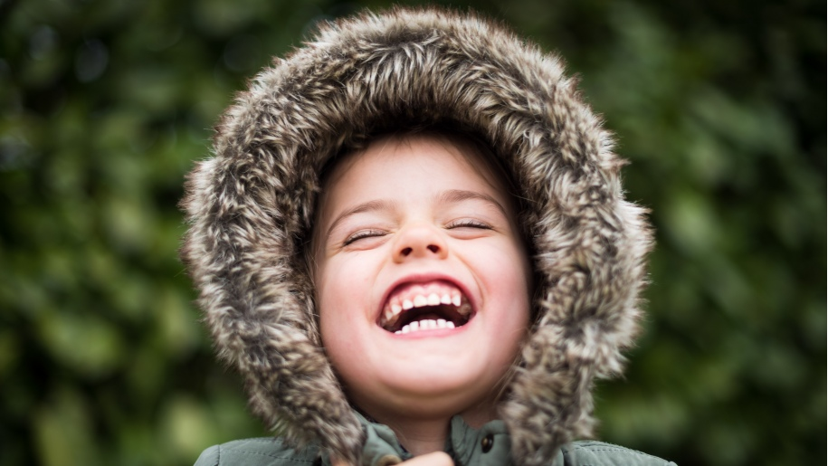 Child laughing wearing winter fur hooded coat