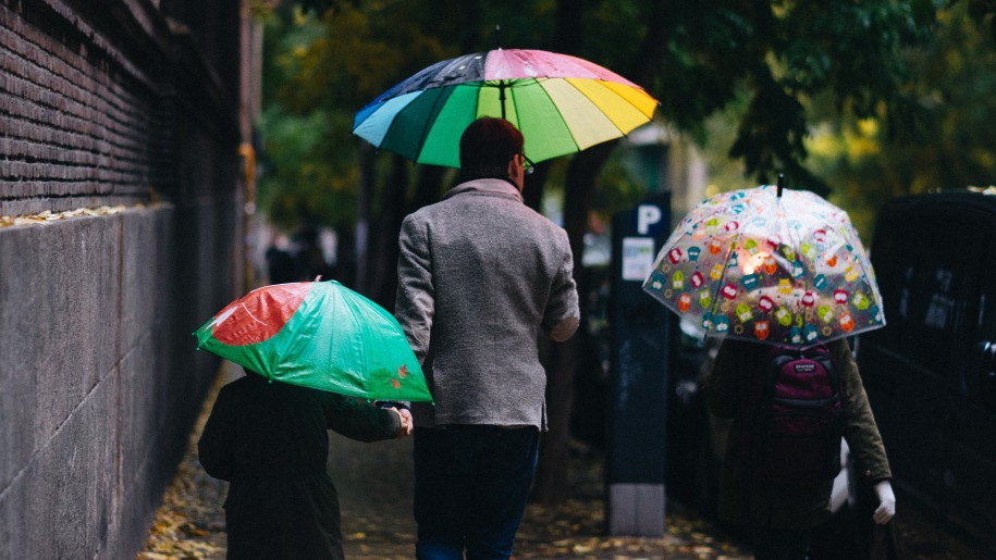 Family walking in the rain with umbrellas