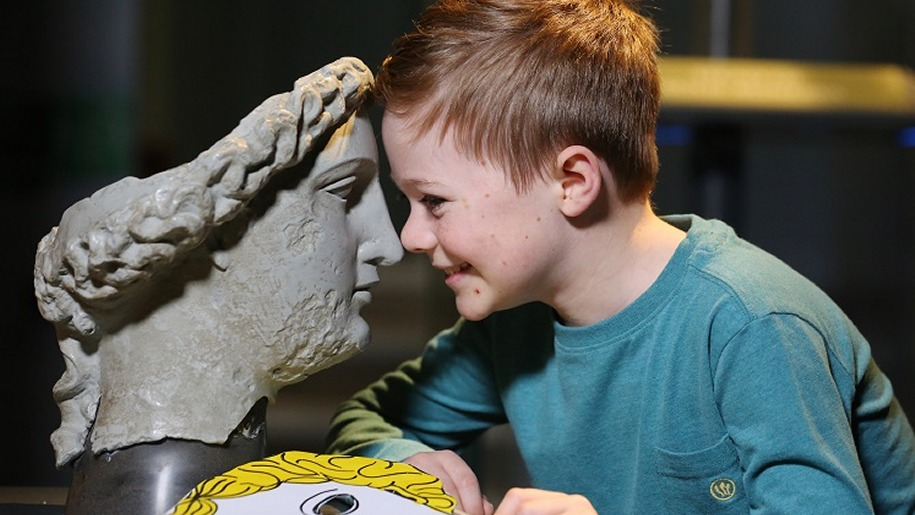 Boy facing Roman mask at Roman Baths