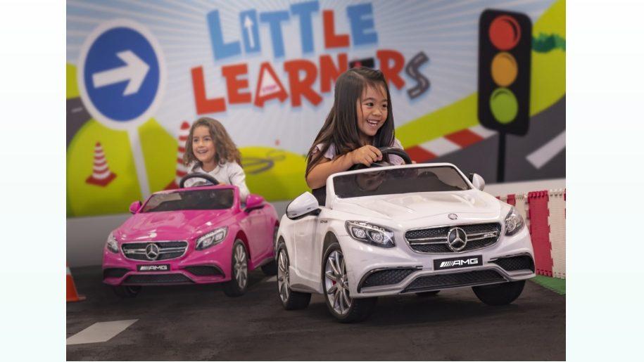 two girls driving mini mercedes cars