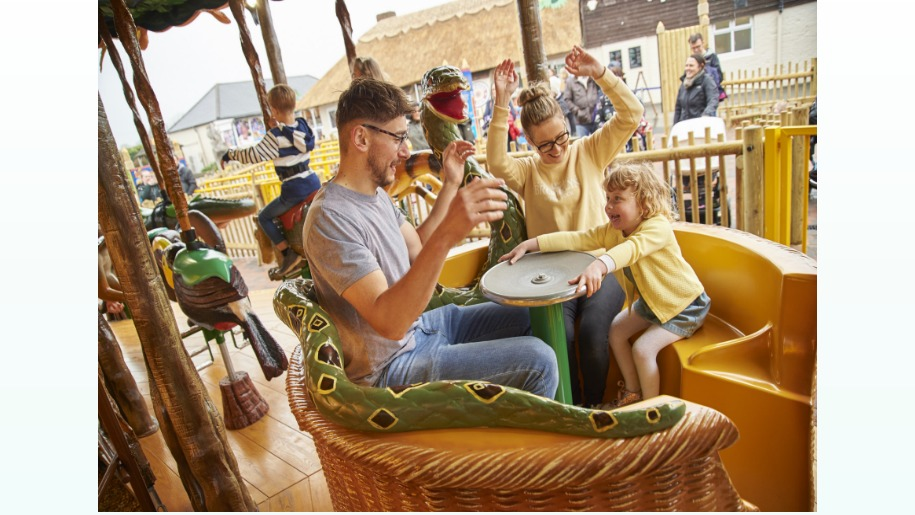 family of 3 in a snake basket carousel ride