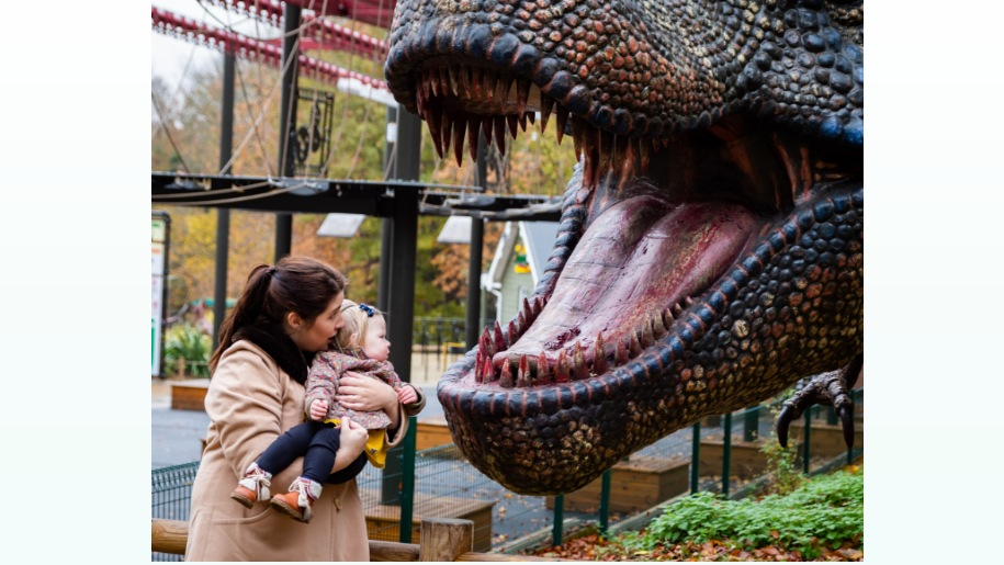 mother & baby standing in front of large dinosaur head