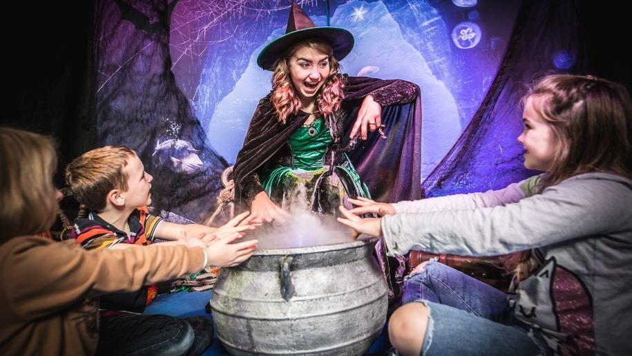 Halloween witch and kids looking at a cauldron at Sea Life