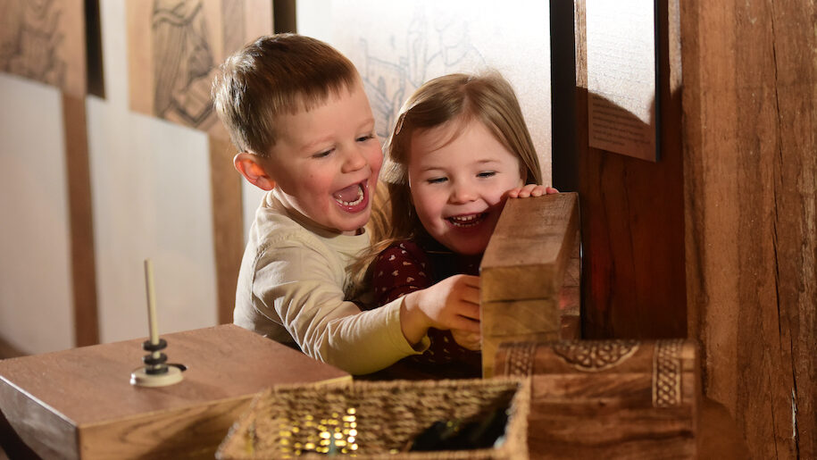 boy and girl playing with wood