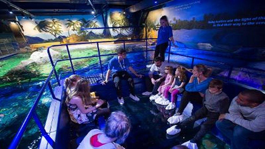 Children in boat going through Brighton aquarium