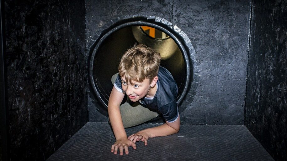 Boy crawling out of tube at Egni Children's Activity Centre