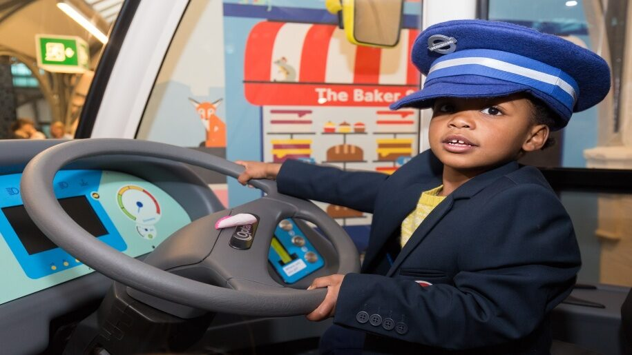 London Transport Museum - child driving a bus wearing a hat