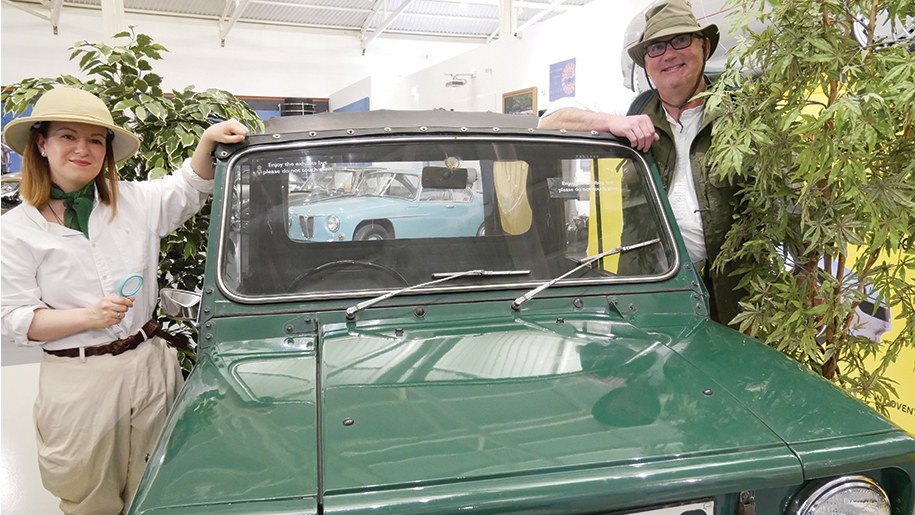 man and woman dressed in safari outfits by a green jeep at British Motor Museum