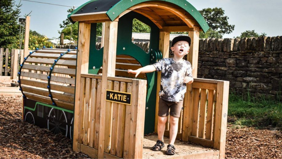 small boy playing on wooden train at Whistlestop Valley