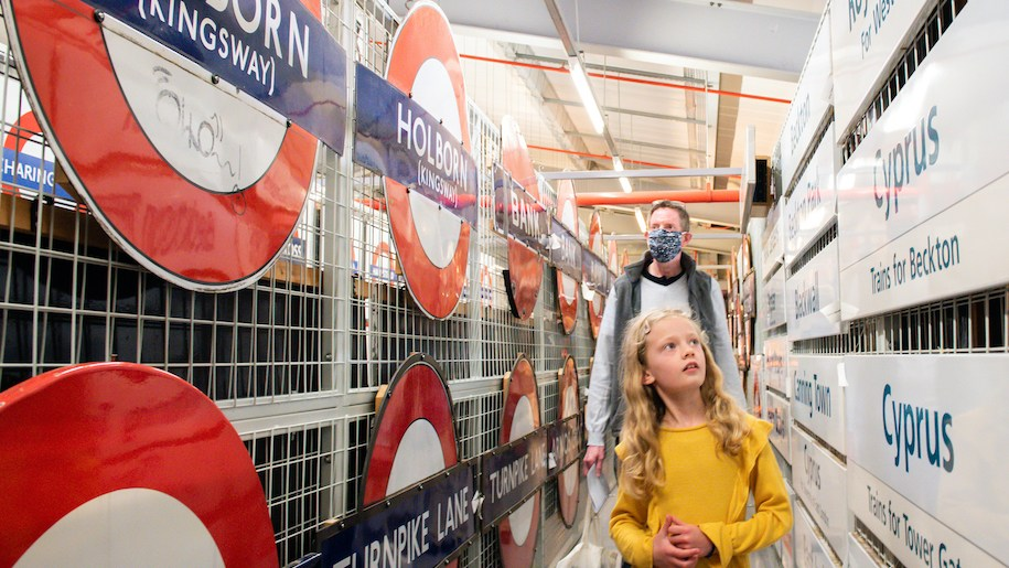 girl and dad looking at tube signs at London Transport Museum