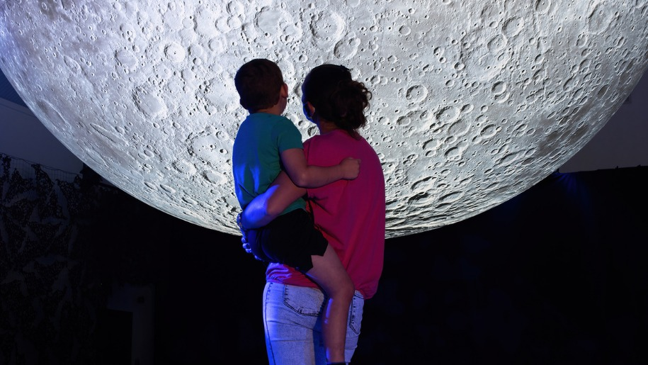 mum carrying toddler looking at giant moon sculpture at Londleat